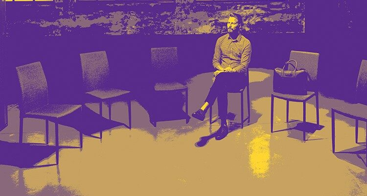 Photo of man sitting in a room of empty chairs.